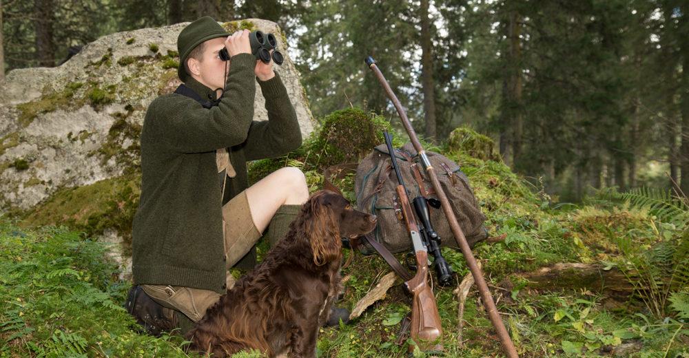 Jäger mit Fernglas, Hund, Jagdstock und Büchse