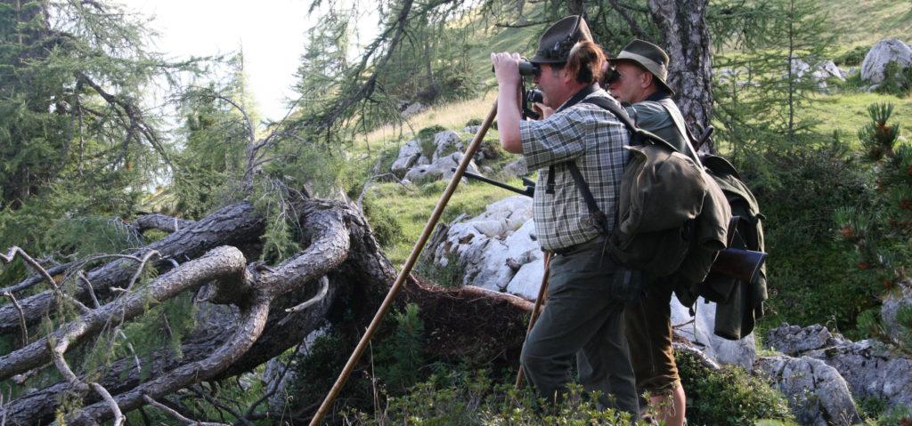 Zwei Jäger mit Jagdstock und Fernglas auf der Pirsch